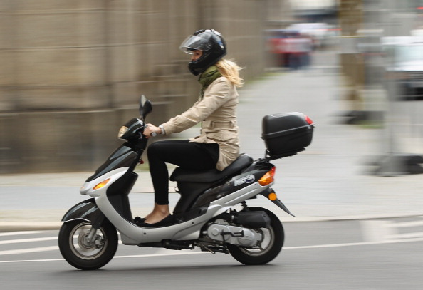 BERLIN, GERMANY - JULY 17:  A young woman rides a moped on July 17, 2012 in Berlin, Germany. Mopeds are a common mode of commuter transportation across Europe.  (Photo by Sean Gallup/Getty Images)